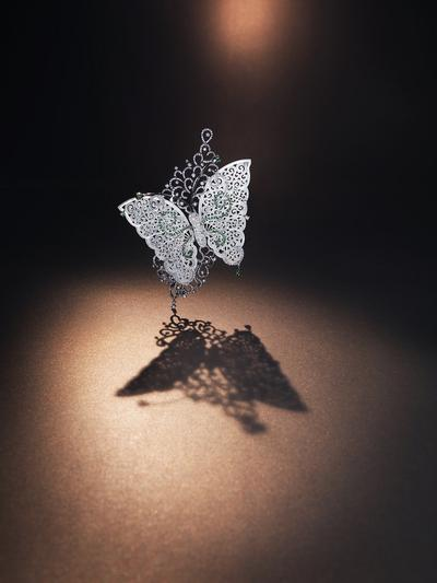 Flying Butterfly, Ammie Kang, An articulated brooch modelled to be a butterfly lying on a leave. The wings are set with 2 icy jadeite carvings decorated by diamonds and tsavorites together weighing approximately 7.03 and 5.49 carats respectively, mounted in 46.13g of 18 karat white gold, signed Kang.