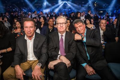 Hollywood action heroes Arnold Schwarzenegger and Sylvester Stallone sit with Edward Tracy, President and Chief Executive Officer of Sands China Ltd., at the Clash in Cotai II at the Venetian Macao's Cotai Arena where Manny Pacquiao defeated Chris Algieri in their WBO world welterweight clash.
