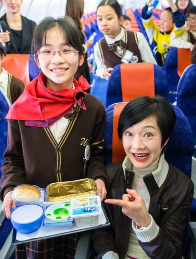 Students dressed in little pilots and little flight attendants' uniforms and carried out in-flight service with the real flight attendants for their very first time