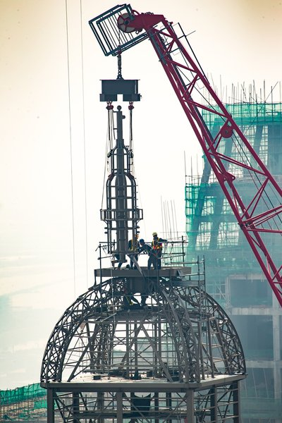 A crane places a lantern atop The Parisian Macao's Eiffel Tower at a topping out ceremony Thursday. Sands China's newest integrated resort and its half-scale replica Eiffel Tower are slated to open in the second half of 2016.