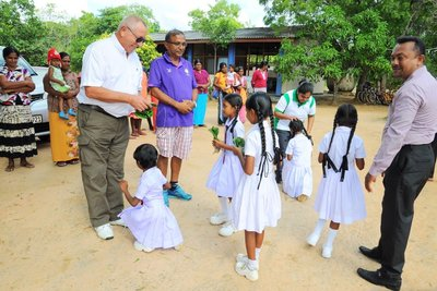 Mr Barry Rawlinson, Chief Executive Officer of Asia Plantation Capital, and Mr Satianathan, client of Asia Plantation Capital, blessing the children of Morapathawa Primary School.