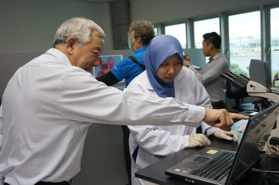 IWK officer showing Dato' Teo the microorganisms living in the water in the lab