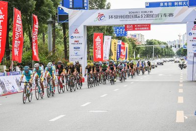 The participating cyclists ride across the starting line after the blast of the starting gun