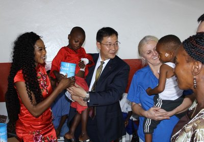 Mrs. Mariatu Kargbo and Mr. Frank Wang distributing milk powder to children