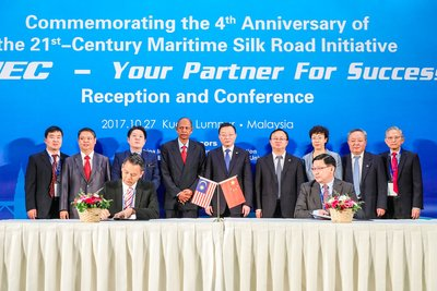 Several important guests, including Malaysia-China Friendship Association president Dato Abdul Majid Khan (fourth from left, back row) and CMEC president Zhang Chun (fifth from left, back row), witness the signing of a cooperation agreement between Chinese and Malaysian companies during the event