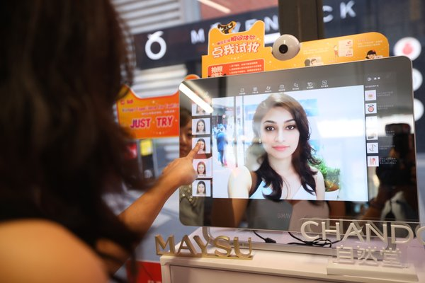 """A customer applying different filters above the """"magic mirror"""""""