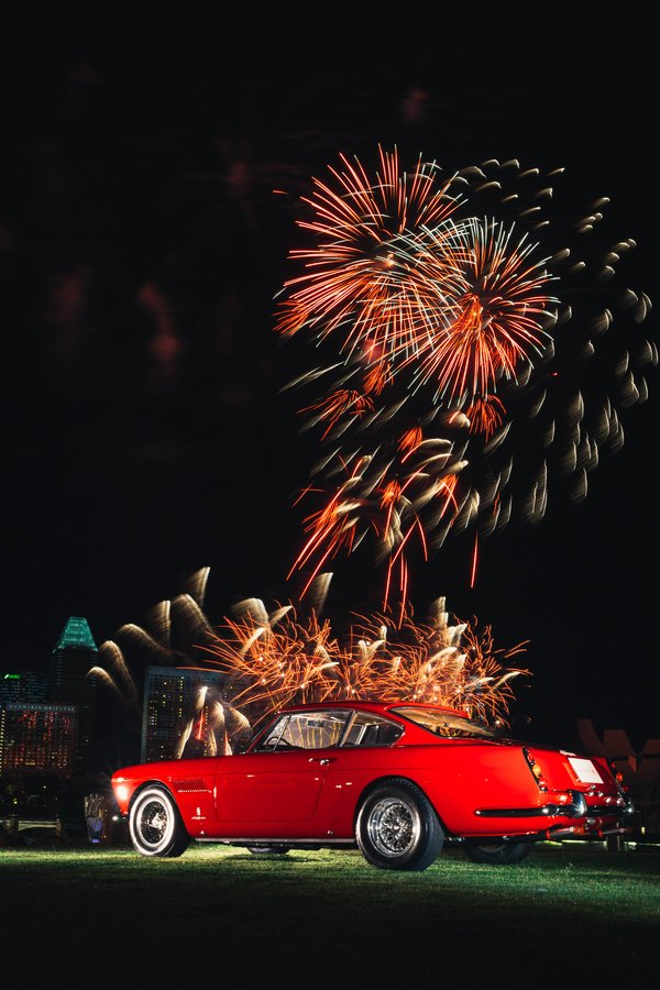 The 1962 Ferrari 250GTE against the panoramic waterfront with fireworks
