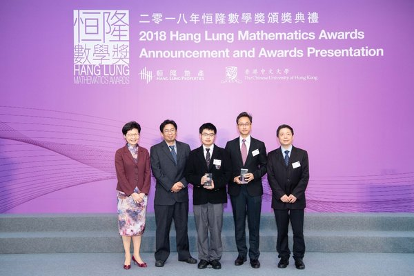"""The Hon Mrs. Carrie Lam Cheng Yuet-ngor, The Chief Executive of the Hong Kong Special Administrative Region, presents the Gold Award of the 2018 HLMA to Zhiyuan Bai (center) from La Salle College for his research paper titled """"On the Trapezoidal Peg Problem among Convex Curves""""."""