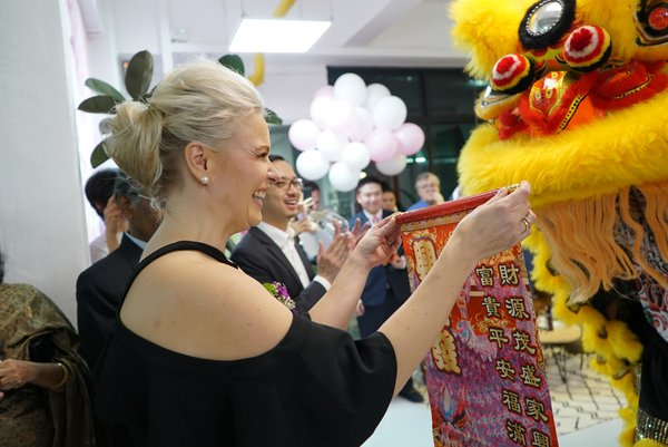 Petra Eratuli-Kola, CEO of Innovation House Finland, receiving a banner from the lion dance of event