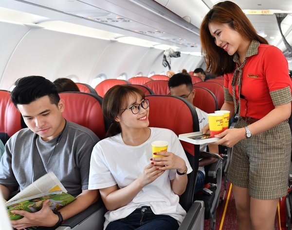A flight attendant serves passengers onboard Vietjet's flight