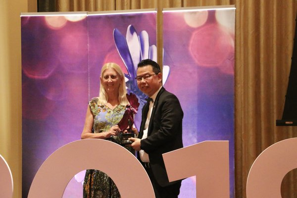 Mr Joseph Siu, Vice President and CEO of Homnicen Group, proudly receiving their LIBA Trophy from Miss Barbara Levy, President of LIA.