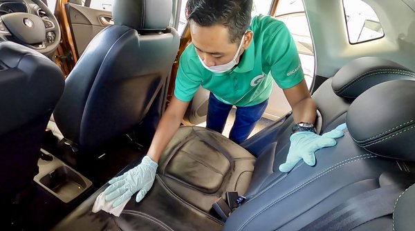 GoCar Fleet Assistant is wiping the backseat with antibacterial wipes.