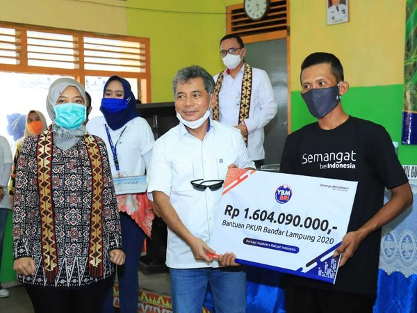 Bank BRI President Director Sunarso (middle) handed over IDR 1.6 billion support from Bank BRI Baitul Mal Foundation (YBM) to 31 farmer groups participating in the People's Business Skills Improvement Program (PKUR) witnessed by Lampung Deputy Governor Hj. Chusnunia Chalim (left) as part of the Food Security Dialogue event with MSMEs at the Bangun Rejo Village Hall, Central Lampung, Thursday (11/06).