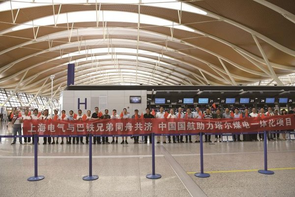 """Holding a banner bearing """"Shanghai Electric joins hand with Pakistan to tide over this difficulty, Air China supports Thar Integrated Coal-Mine power projectâ€, Shanghai Electric team gathered at the airport terminal to say their goodbyes before the deployment journey to Karachi."""