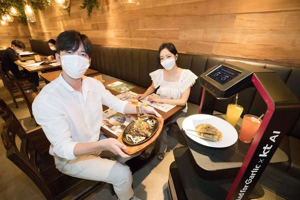 Models introduce an AI robot server at the Mad for Garlic restaurant in Hyundai I-Park Tower, Gangnam District, Seoul, South Korea, on September 1, 2020.