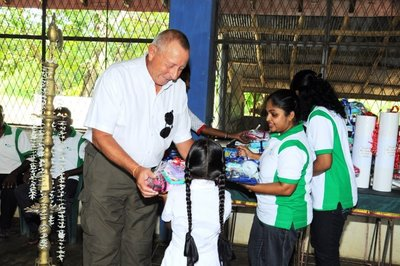 Mr Barry Rawlinson, CEO of Asia Plantation Capital, giving out sponsored gifts to the children of Morapathawa Primary School.