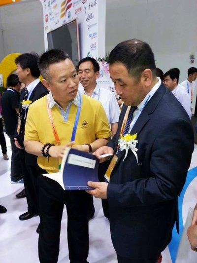 张宏宇向外贸发展局局长孙成海介绍特乐意建材交易平台
