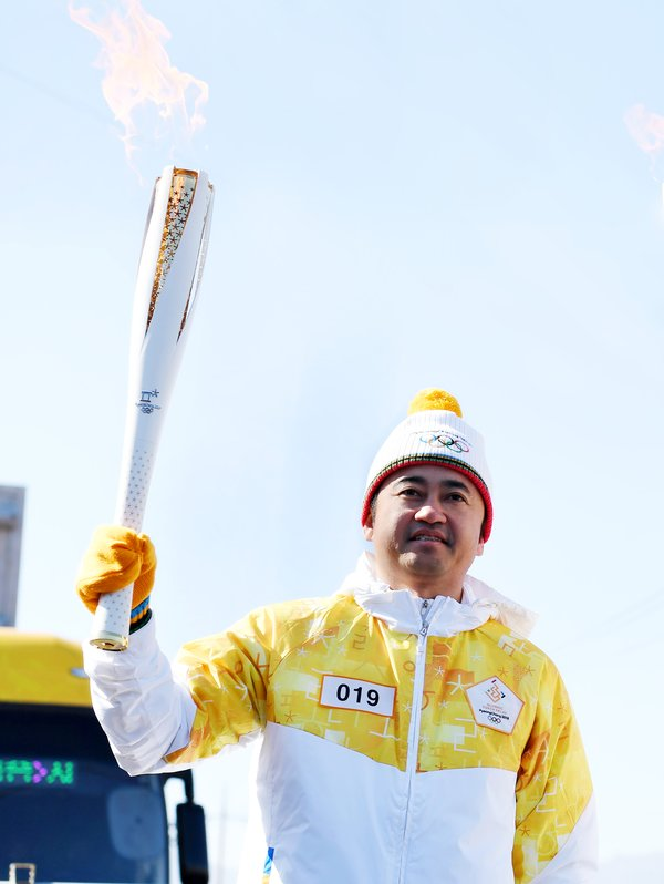 Ding Shizhong, Board Chairman of ANTA Sports, carries the torch for the Olympics.