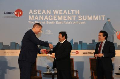 From left: Yuri Bender, Editor-in-Chief, Professional Wealth Management presenting a token of appreciation to Dato' Mohammed Azlan Hashim, Chairman of Labuan IBFC Inc. Standing in the far right is Saiful Bahari Baharom, Chief Executive Officer of Labuan IBFC Inc