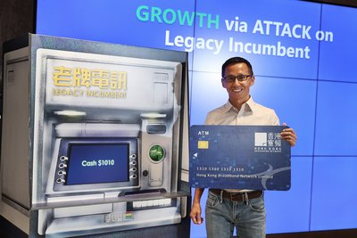 Drawing cash with a mock ATM card, HKBN CEO and Co-Owner William Yeung illustrates our company's strategy to accelerate revenue growth through ATM: A/xDSL broadband (A), telephone line (T) and mobile services (M).