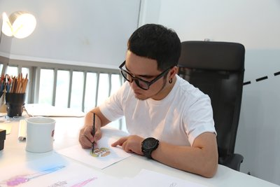 Chinese designer Big-King sketches a GuangYuYuan inspired design for his Paris Fashion Week Debut