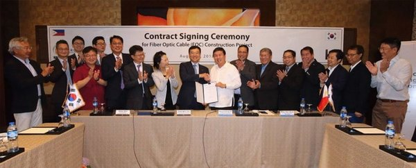 Yun Kyoung-Lim, ninth from left, head of KT's future convergence and global businesses, and Dennis Anthony H. Uy, 10th from left, CEO of Converge ICT Solutions Inc., and other representatives from the two companies are photographed during a signing ceremony for the construction of an optical fiber network in Luzon, held at EDSA Shangri-La in Manila on August 8.