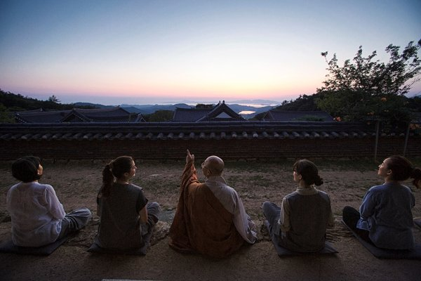A monk and Templestay participants watching the sunset in Mihwangsa Temple