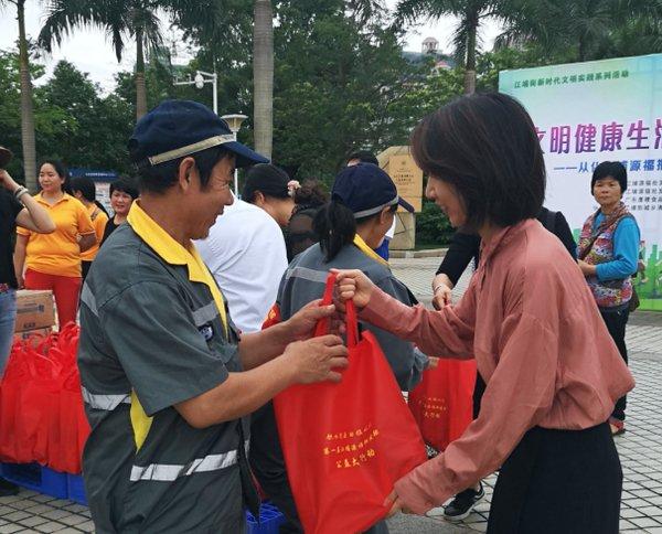环卫工人开心地接过李锦记工作人员赠送的礼品