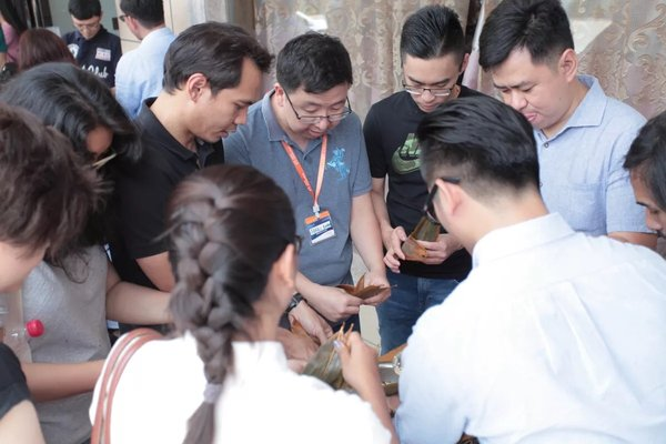 Participants of the eFounders fellowship program organized by Alibaba Business School and UNCTAD try their hands at zongzi wrapping in Bainiu Village