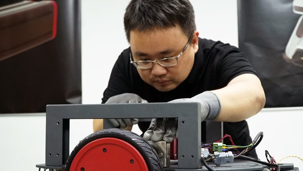 Luo Xuan, co-founder and General Manager of Syrius Robotics, gives final check for AMR production.