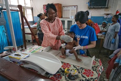 Trip.com volunteer helps to measure the nutrition level of a child at a local clinic.