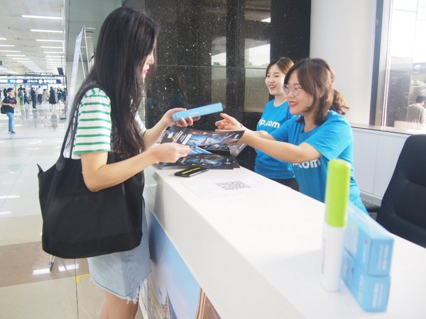 Travelers receiving information and gifts from Trip.com Travel Concept Pop-Up Counter at Gimpo Airport, South Korea