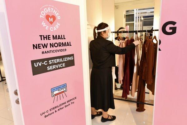 商场工作人员在UV- C消毒间准备对衣物进行消毒