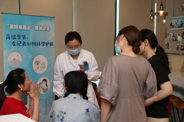 皮肤科专家于活动现场为女性记者进行义诊